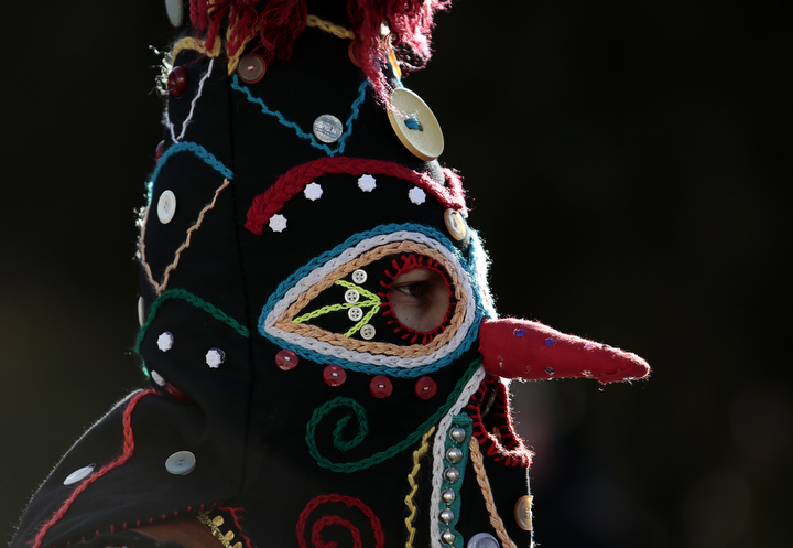 """A masked Bulgarian dancer takes part in the second competition day of the 24th International Festival of Masquerade Games """"Surva"""" in the town of Pernik, Bulgaria. Some 5,000 people are expected to take part in the three-day festival devoted to an ancient Bulgarian pagan rite. Surva is performed by costumed men, some in sheepskin, or other colorful garments, bells and masks, who walk around and dance to scare away the evil spirits, in hope to provide a good harvest, health, fertility, and happiness. (Valentina Petrova/AP Photo)"""
