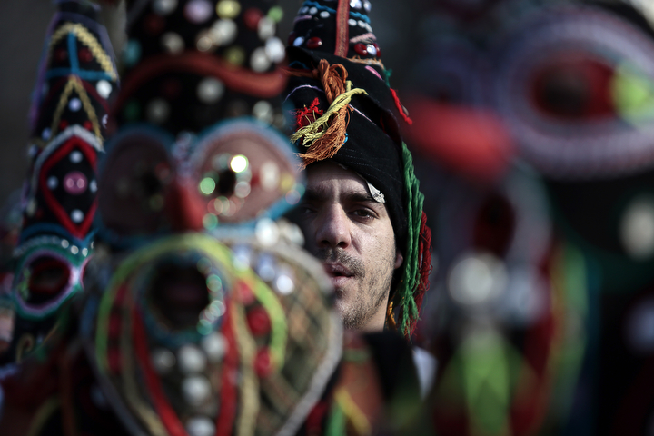 """A Bulgarian dancer is seen between masks as they take part in the second competition day of the 24th International Festival of Masquerade Games """"Surva"""" in the town of Pernik, Bulgaria. Some 5,000 people are expected to take part in the three-day festival devoted to an ancient Bulgarian pagan rite. Surva is performed by costumed men, some in sheepskin, or other colorful garments, bells and masks, who walk around and dance to scare away the evil spirits, in hope to provide a good harvest, health, fertility, and happiness. (Valentina Petrova/AP Photo)"""