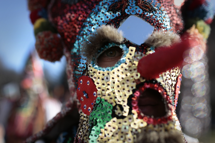 """A Bulgarian dancer looks on behind his mask as they take part in the second competition day of the 24th International Festival of Masquerade Games """"Surva"""" in the town of Pernik, Bulgaria. Some 5,000 people are expected to take part in the three-day festival devoted to an ancient Bulgarian pagan rite. Surva is performed by costumed men, some in sheepskin, or other colorful garments, bells and masks, who walk around and dance to scare away the evil spirits, in hope to provide a good harvest, health, fertility, and happiness. (Valentina Petrova/AP Photo)"""