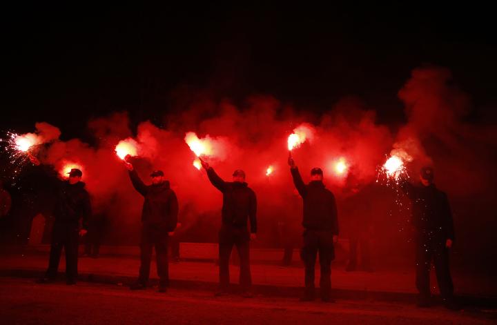 """Supporters of Greece's extreme right party Golden Dawn hold flares during a rally to commemorate a 1996 incident which cost the lives of three Greek navy officers and brought Greece and Turkey to the brink of war, in Athens. The extreme right, anti-immigrant Golden Dawn party, which has Nazi roots, appears headed for a third-place finish in last Sunday's election. Its showing comes despite the fact that the party's leader and most of its lawmakers are behind bars, facing charges of participating in a """"criminal organization"""" accused of murders, brutal attacks on migrants and others, extortion and arson. (Lefteris Pitarakis/AP Photo)"""