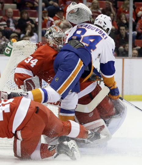 New York Islanders center Mikhail Grabovski (84) crashes into Detroit Red Wings goalie Petr Mrazek (34), of the Czech Republic, during the first period of an NHL hockey game in Detroit. (Carlos Osorio/AP Photo)