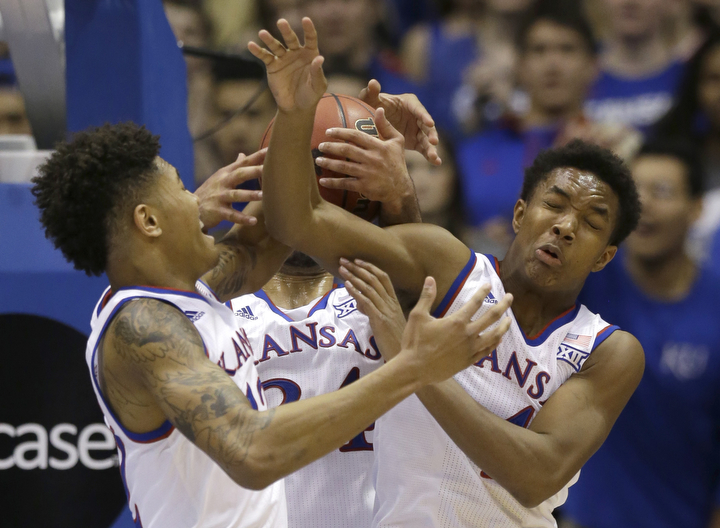 Kansas guards Kelly Oubre Jr., left, guard Devonte Graham, right, and forward Perry Ellis, back, vie for a rebound during the first half of an NCAA college basketball game against Kansas State in Lawrence, Kan. (Orlin Wagner/AP Photo)
