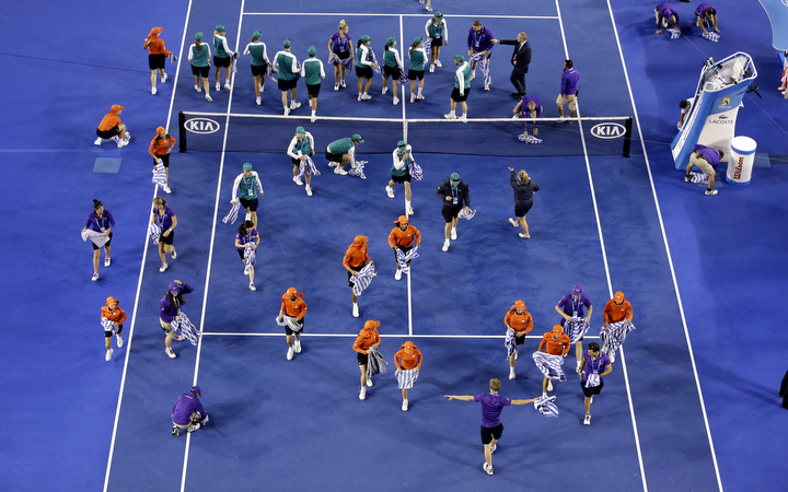 Ground staff dry the court surface of Rod Laver Arena in the rain delay during the women's singles final between Serena Williams of the U.S. and Maria Sharapova of Russia at the Australian Open tennis championship in Melbourne, Australia, Saturday. (Lee Jin-man/AP Photo)