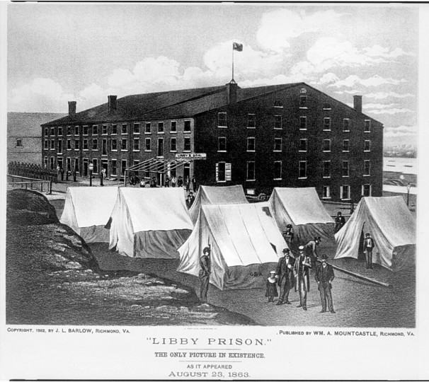 "Title: ""Libby Prison."" The only picture in existence. As it appeared August 23, 1863 / A. Hoen & Co. Richmond, Va. --  Print shows three men and a child standing in the foreground with tents labeled ""C.S.A."" immediately behind them and the Libby Prison building in the background. (A. Hoen & Co./Library of Congress)"