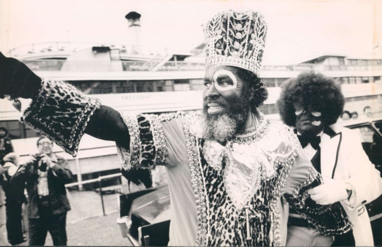 Carnival King Zulu has an aide tug at his arm to get him started in the right direction as he began his reign on Tuesday, March 2, 1976 in New Orleans. Behing the royal makeup is Rev. Lawler P. Daniels who srated his day with a river cruise (AP Wirephoto)