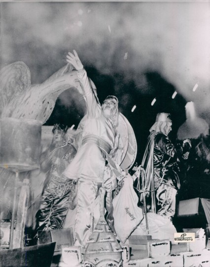 "Original cutline: ""The carnival float appears to be something from Hades with the eerie cloud of smoke around the revelers in the Krewe or Momus parade. Actually the smoke was created by flaming torches lighting the way for this typical Mardi Gras scene in New Orleans. And the bag the reveler is holding contains trinkets for the crowd not laundry, as labeled."" (AP Wirephoto, 1966)"