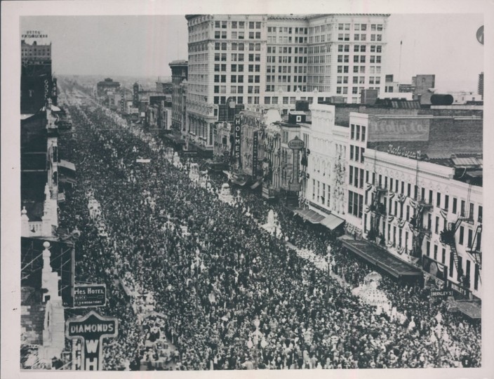 "Original cutline: ""A view of crowd-packed Canal Street during the parade of floats on February 9, 1937, when half of a million celebrants cast aside their everyday cares and turned out to observe the century-old Mardi Gras. The chief interest of teh merry-making throng centered around the float of Rex, Lord of Misrule and king of the whole carnival."" (World Wide Photo)"