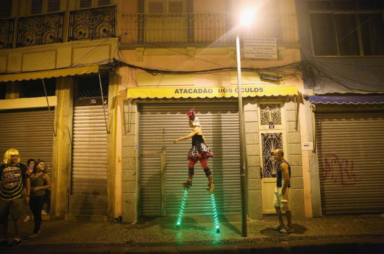 A stilt-walker strides towards revelers during the My Light is LED 'bloco' pre-Carnival street parade on February 12, 2015 in Rio de Janeiro, Brazil. Carnival runs this year February 13-17.    Photo by Mario Tama/Getty Images
