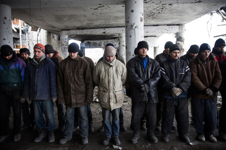 Ukrainian soldier prisoners-of-war are lined up before being forced by pro-Russian rebels to search through the wreckage of the destroyed Donetsk airport for weaponry and dead bodies on February 26, 2015 in Donetsk, Ukraine. The Donetsk airport has been one of the most heavily fought over pieces of land between the Ukrainian army and pro-Russian rebels. (Photo by Andrew Burton/Getty Images)