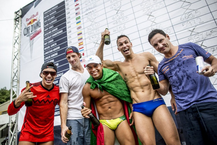 This handout photo received from Red Bull and taken on February 7, 2015 shows the five divers now qualified to join the 2015 World Series (L-R) Jonathan Paredes of Mexico, Andy Jones of the USA, Jucelino Junior of Brazil, Michal Navratil of the Czech Republic and Blake Aldridge of the UK celebrating in front of the score board after the final rounds of the Red Bull Cliff Diving World Series qualification competition at Piscinas Panamericanas, Cali, Colombia. The five divers will join the five pre-qualified divers from last year in the 2015 season. Dean Treml/AFP/Red Bull/Getty Images