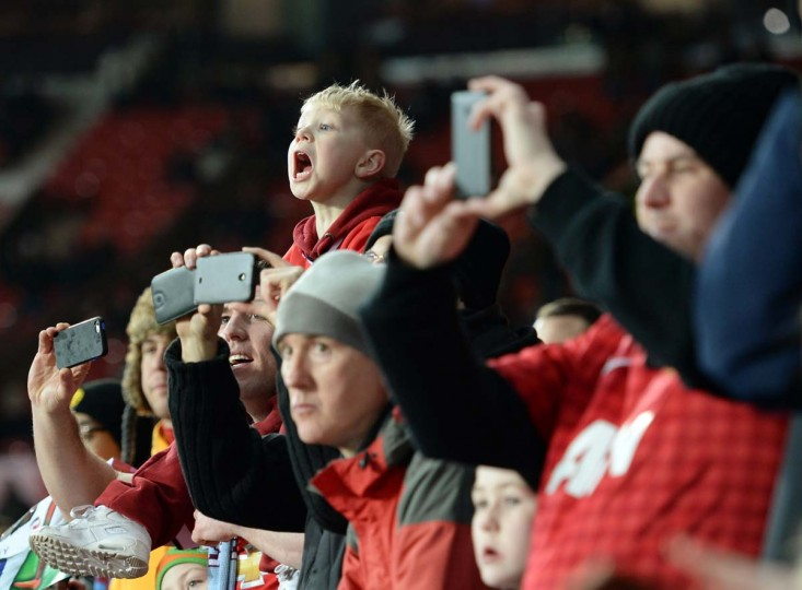 A young Manchester United fan shouts out to the players as they warm-up prior to the English Premier League football match between Manchester United and Burnley at Old Trafford in Manchester, north west England, on February 11, 2015. Manchester United won the game 3-1.     CREDIT: OLI SCARFF - AFP/GETTY IMAGES