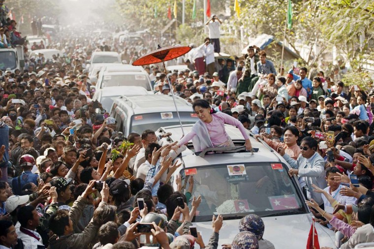 Myanmar opposition leader Aung San Suu Kyi (C) greets supporters as she leaves celebrations to mark the 100th birthday of the country's independence hero, her father Aung San, in the remote central Myanmar town of Natmauk on February 13, 2015. Myanmar's Aung San Suu Kyi addressed a crowd of thousands in the biggest celebrations honouring her independence hero father in memory, underscoring her legacy months before leading the opposition to momentous elections.            CREDIT: YE AUNG THU - AFP/GETTY IMAGES