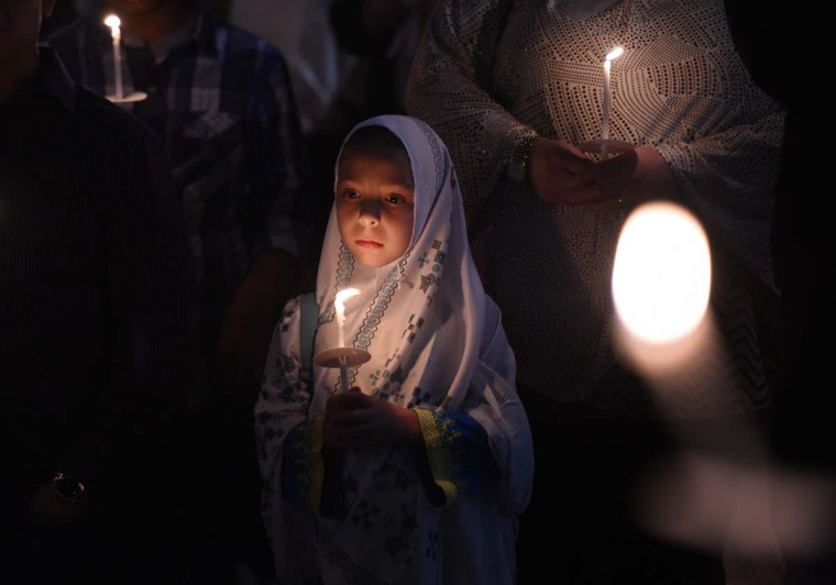 A young Muslim girl holds a candlelight during a vigil  at the Islamic Center of Southern California in Los Angeles on February 12, 2015  for the three Muslim students who were fatally shot in  North Carolina.    The families of three Muslim students shot dead by a white neighbor have reiterated calls for the killings to be treated as a hate crime.           CREDIT: MARK RALSTON - AFP/GETTY IMAGES