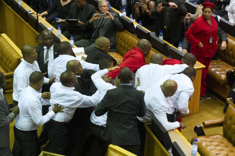 Members of the Economic Freedom Fighters, wearing red uniforms, clash with security forces during South African President's State of the Nation address in Cape Town on February 12, 2015. Security forces were called to eject radical lawmakers who interrupted South African President Jacob Zuma's annual state of the nation address to parliament. The members of the Economic Freedom fighters led by populist firebrand Julius Malema had caused uproar as they demanded that Zuma repay millions of taxpayers money spent on his private residence.    CREDIT:RODGER BOSCH/AFP/GETTY IMAGES