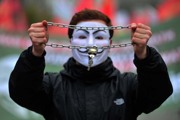 A high school student wears a Guy Fawkes mask and holds a locked chain during a demostration in Istanbul on February 13, 2015. A boycott of schools was launched on Feb. 13 upon a call from the teachers union and a number of Alevi associations to protest the government's recent education system implementations, including on compulsory religion classes.     CREDIT: OZAN KOSE - AFP/GETTY IMAGES