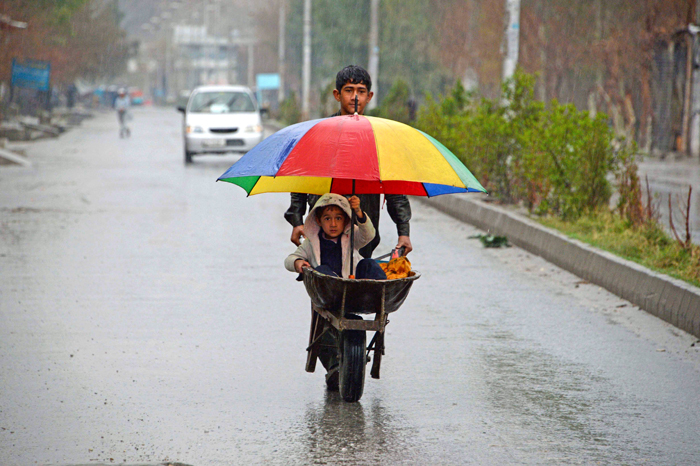 An Afghan boy pushes a wheelbarrow carrying his brother during a rainy day on the outskirts of Jalalabad on Tuesday. (Noorullah Shirzada/AFP/Getty Images)