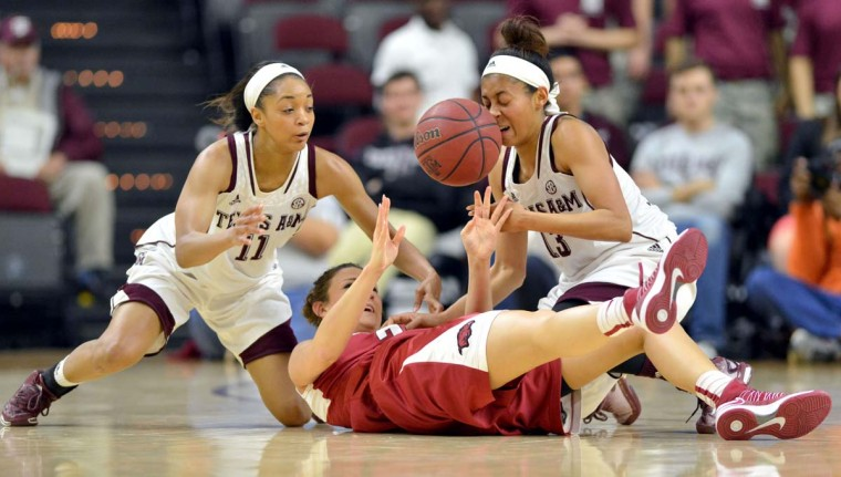 Texas A&M's Curtyce Knox, left, and Chelsea Jennings, right, juggle the ball away from Arkansas' Katie Powell during the first half of an NCAA basketball game, Thursday, Feb. 12, 2015, in College Station, Texas. Texas A&M won 59-55.     CREDIT: COLLEGE STATION EAGLE, SAM CRAFT - AP PHOTO
