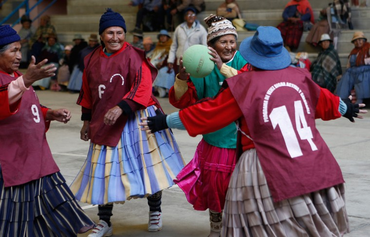 In this Feb. 11, 2105 photo, 72-year-old Aurea Murillo prepares to make a pass during a handball match among elderly Aymara indigenous women in El Alto, Bolivia. Dozens of traditional Aymara grandmothers ease many of the aches and pains of aging by practicing a sport that is decidedly untraditional in Bolivia: team handball. (AP Photo/Juan Karita)