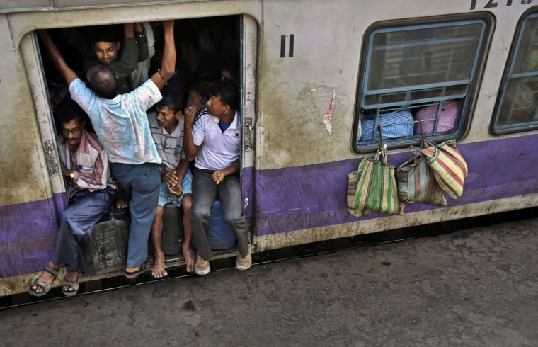 Indian passengers crowd the doorway of one of the coaches of a suburban train as it prepares to leave a station on the outskirts of Kolkata, India, Thursday, Feb. 26, 2015. Indian Railway minister Suresh Prabhu Thursday unveiled the budget for one of the world's largest railways systems that serves more than 23 million passengers a day. (Bikas Das/AP Photo)