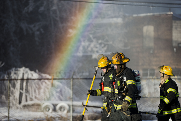 Firefighters walk past refracted light and a building covered in ice from their water canons as they battle a blaze, Tuesday in the Kensington neighborhood of Philadelphia. The fire started in a building housing retail shops. No injuries were reported. (Matt Rourke/AP)