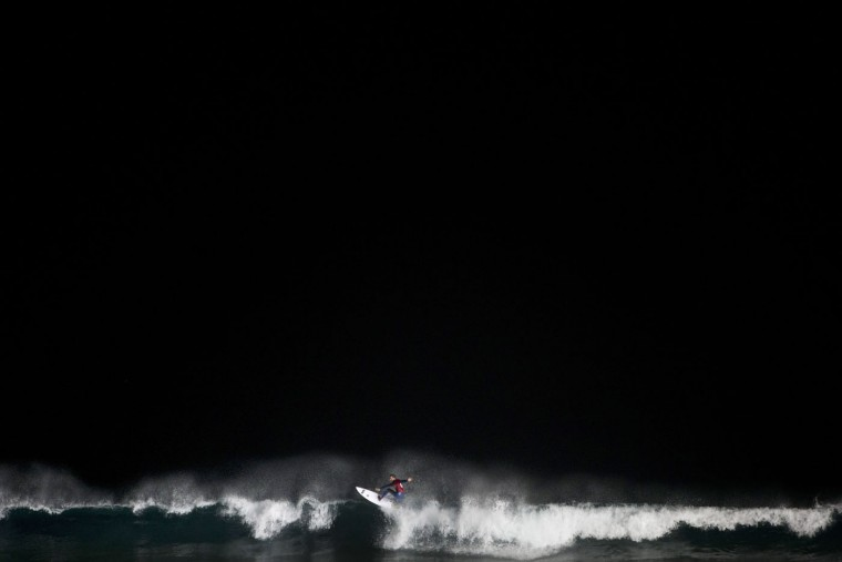 An Israeli surfer catches a wave during a night surfing competition in the Mediterranean sea in Ashdod, southern Israel, Wednesday, Feb. 4, 2015. About 40 surfers participated in the competition which started Wednesday after sundown. (AP Photo/Oded Balilty)