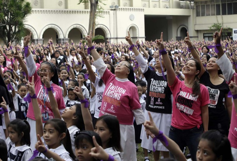 With purple ribbons on their wrists, more than 3,000 students, teachers and nuns from the Catholic-run St. Scholastica's College in Manila, flash the No.1 sign as they dance at their quadrangle to take part in the global campaign to end violence against women and girls dubbed One Billion Rising, Friday, Feb. 13, 2015 in Manila, Philippines.     CREDIT: BULLIT MARQUEZ - AP PHOTO