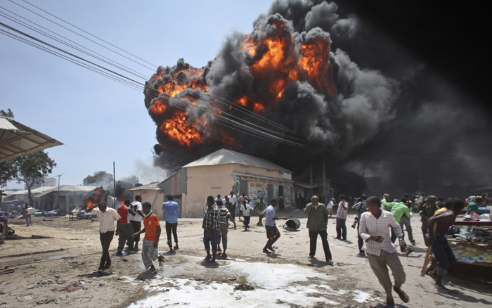 Somalis run from an explosion during a fire that engulfed a fuel market, causing extensive property damage but no loss of life, in the Hodan district of the capital Mogadishu on Monday. Mogadishu has a fire brigade but few firefighting vehicles, making it difficult to deal with such incidents in the city, which is still recovering from decades of war. (Farah Abdi Warsameh/AP)