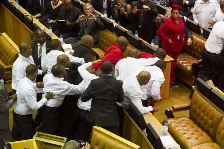 South African Economic Freedom Fighters, EFF, disrupt the official opening session inside Parliament while security personnel dressed in white shirts try and stop the action in Cape Town, South Africa, Thursday, Feb. 12, 2015. Security guards entered South Africa's parliament on Thursday to remove opposition lawmakers who disrupted an annual address by President Jacob Zuma to demand that he answer questions about a spending scandal. (Rodger Bosch/Pool/AP)