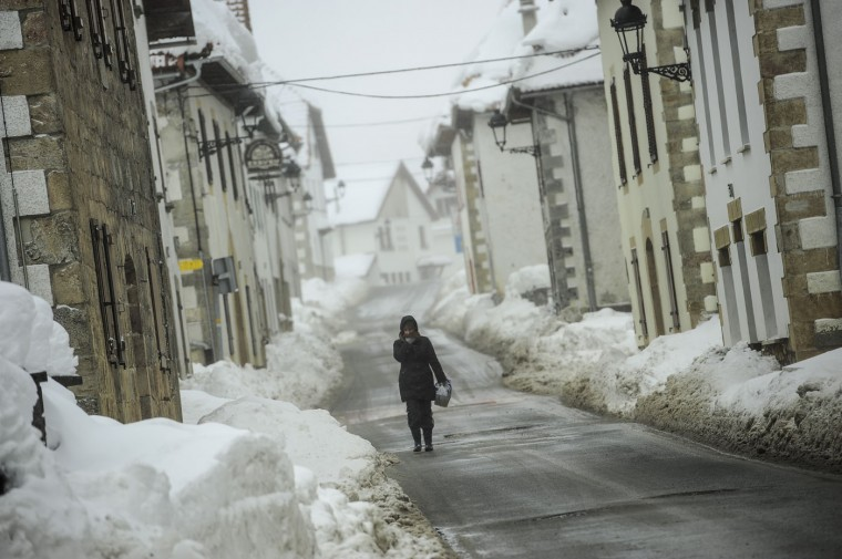 A woman walks along the road on a winter's day in the small town of El Espinal, in the Pyrenees mountains in northern Spain, Thursday, Feb. 5, 2015. A cold spell has reached northern Spain with temperatures plummeting far below zero. (AP Photo/Alvaro Barrientos)