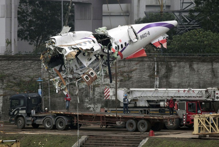 The main fuselage from TransAsia Airways Flight 235 is hoisted away in Taipei, Taiwan, Thursday, Feb. 5, 2015. The commercial plane, with 58 people aboard, clipped a bridge shortly after takeoff and crashed into a river in the island's capital of Taipei on Wednesday morning. (AP Photo/Wally Santana)