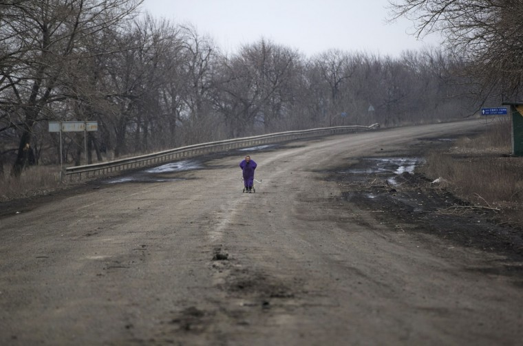 An elderly woman drags a cart with belongings on the outskirts of Debaltseve, Ukraine, Thursday, Feb. 26, 2015. After weeks of relentless fighting, which inflicted severe damage to most buildings, the embattled Ukrainian rail hub of Debaltseve fell last week to Russia-backed separatists. (Vadim Ghirda/AP Photo)