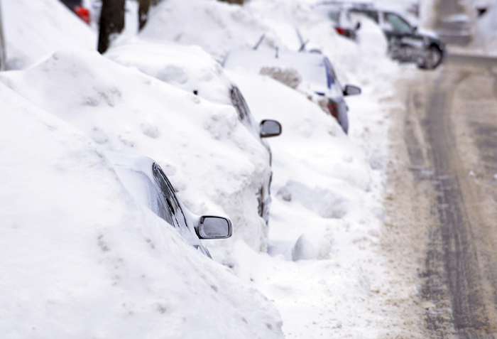 A line of cars sit buried in snow banks in Somerville, Mass., Tuesday.(Josh Reynolds.AP)