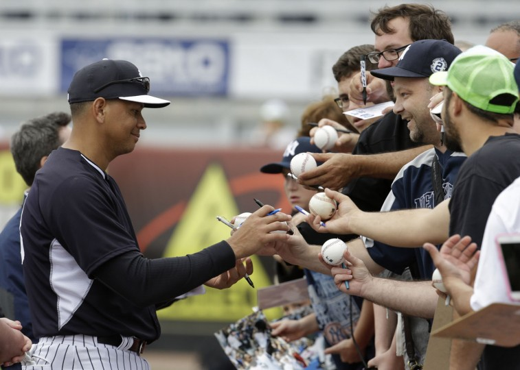 New York Yankees' Alex Rodriguez signs autographs for fans during a spring training baseball workout, Thursday, Feb. 26, 2015, in Tampa, Fla. (Lynne Sladky/AP Photo)