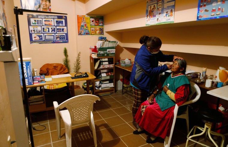 In this Feb. 11, 2105 photo, a doctor checks Aurea Murillo's eyes during a general health check-up after Murillo played a handball game in El Alto, Bolivia. Older people practice sports, play Andean music and recall their younger years through the city sponsored health program that also provides free medical care. (AP Photo/Juan Karita)