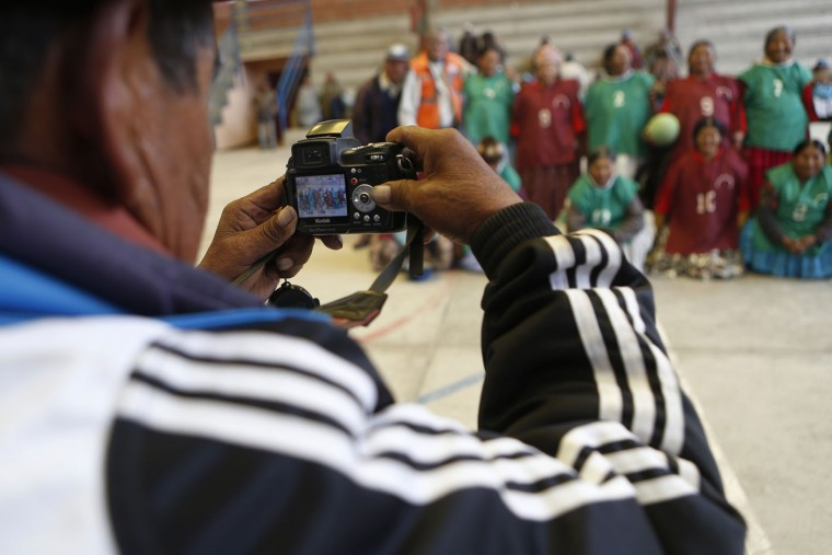 In this Feb. 11, 2105 photo, a photographer takes a group picture of elderly Aymara indigenous women who play handball together in El Alto, Bolivia. The city's health program for seniors so far has spread to almost half of the city's districts. (AP Photo/Juan Karita)