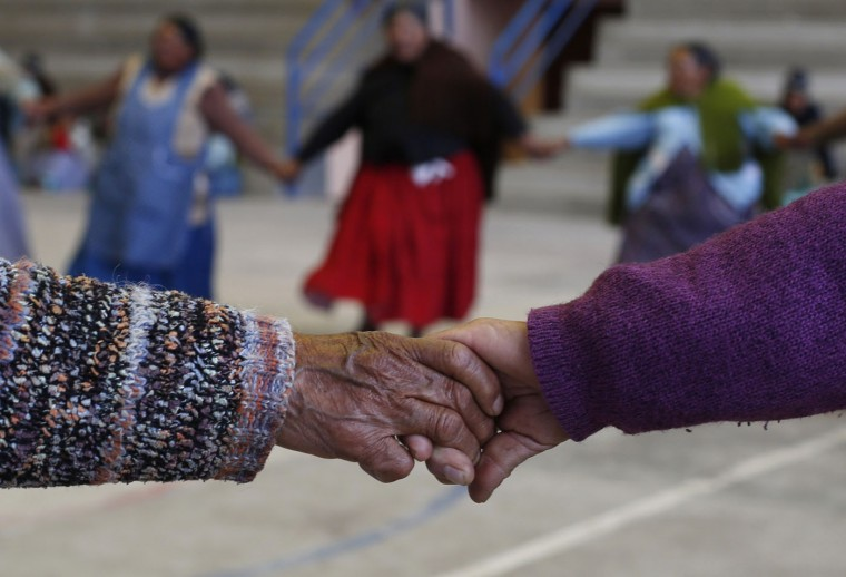 In this Jan. 28, 2105 photo, elderly Aymara indigenous women warm up before playing handball in El Alto, Bolivia. ìThere are days my knees hurt from rheumatism, but when I play it goes away,î said 77-year-old Rosa Lima, who first began doing simple exercises eight years ago, then later took up team handball. She lives alone and looks forward to playing with her friends every week. (AP Photo/Juan Karita)