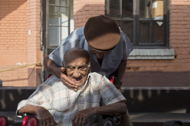 "Veteran clown Ricardo Farfan, popularly known as ""Pitito,"" top, says goodbye to his friend Emilio Perez who celebrated his 102nd birthday at the nursing home in Lima, Peru. Although Farfan worked his entire life at his family's circus, starting when he was three-years-old in 1927, and ran it for decades to support his family, the government does not give monthly pension payments to circus artists, so his four children support him financially. (AP Photo/Esteban Felix)"