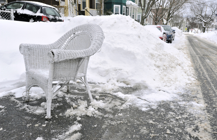 A patio chair stakes a claim to a parking space cleared of snow  in Somerville, Mass., Tuesday. The latest snowstorm left the Boston area with another two feet of snow and forced the MBTA to suspend all rail service for the day. (Josh Reynolds/AP)