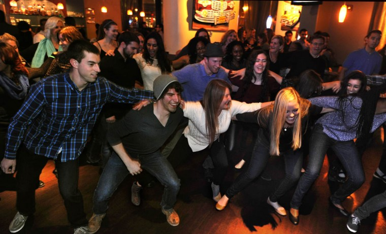 Salsa students link arms as they practice their footwork at the last Monday night salsa party at Talara. (Algerina Perna/Baltimore Sun)