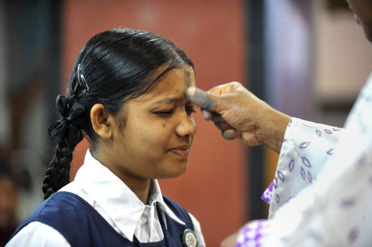 Indian Archbishop of Hyderabad Thumma Bala (right) marks the symbol of the cross with ash on the forehead of a young Christian devotee during an Ash Wednesday service at Saint Mary's Basilica in Secunderabad, the twin city of Hyderabad, on February 18, 2015. (NOAH SEELAM/AFP/Getty Images)