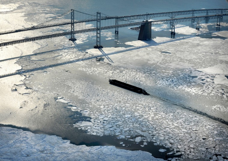 A tugboat pushes a barge through the ice and toward the Bay Bridge. (Lloyd Fox/Baltimore Sun)