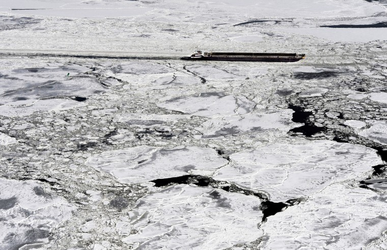A tugboat pushes a barge through the Chesapeake Bay ice as it heads towards the Bay Bridge. (Lloyd Fox/Baltimore Sun)