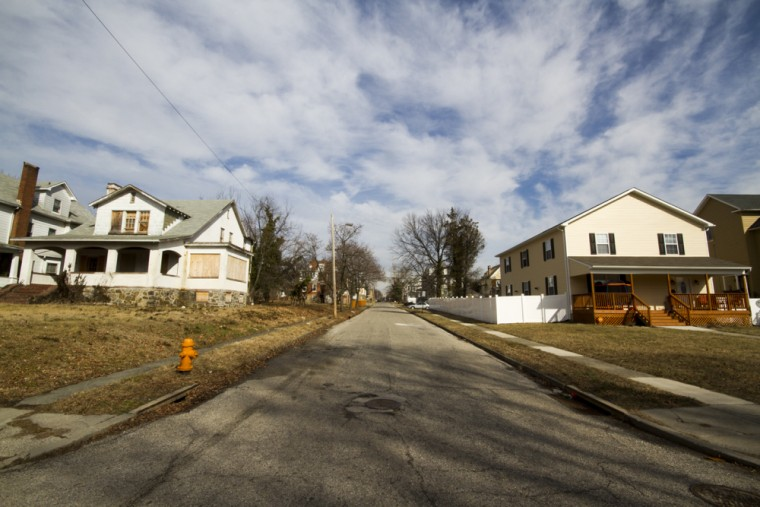 Signs of rehabilitation crop up around the neighborhood with new construction on older lots, or with older vacant homes being bought and rehabilitated. To the left, a dilapidated home sits parallel to a newly built home. (Kalani Gordon, Baltimore Sun, Feb. 2015)