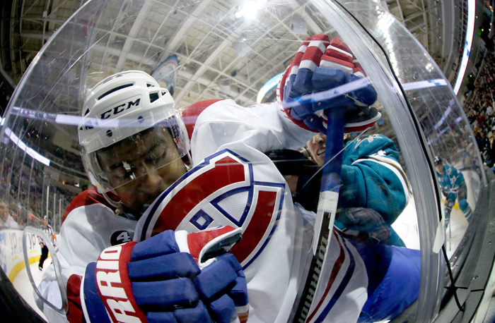 Devante Smith-Pelly of the Montreal Canadiens is checked into the glass by Brenden Dillon of the San Jose Sharks at SAP Center on Monday in San Jose, California. (Ezra Shaw/Getty Images)