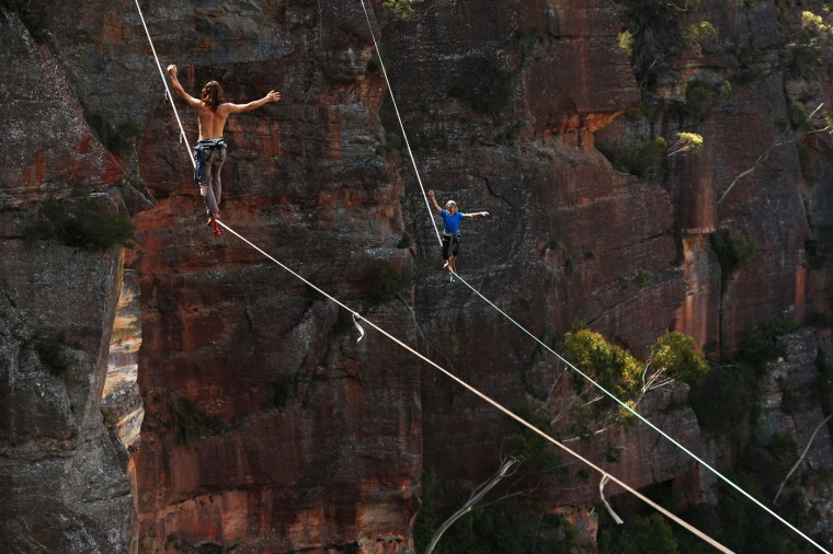 Guilherme Lopes of Brazil walks on a 60m highline (L) and Joseph Huard of Canada (R) walks on a 90m highline rigged between cliffs at Corroboree Walls in Mount Victoria on March 8, 2015 in the Blue Mountains, Australia. (Photo by Cameron Spencer/Getty Images)