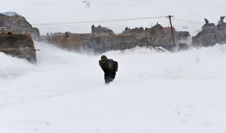 An Afghan survivor of an avalanche runs to get relief goods distributed by an Afghan army helicopter in the Paryan district of Panjshir province, north of Kabul on March 1, 2015. Afghan President Ashraf Ghani February 28 pledged to set up a relief fund for the victims of avalanches that claimed over 280 lives, and called for international help with the relief effort. (Shah Marai/AFP/Getty Images)