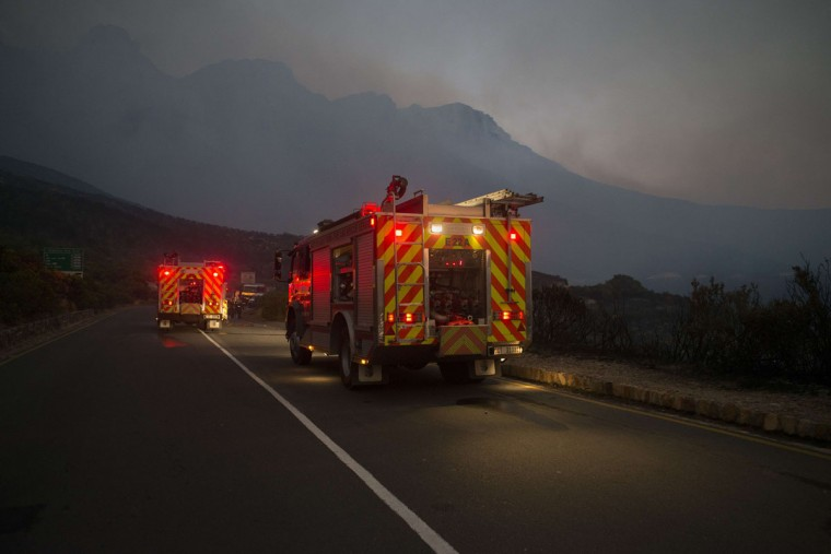 Fire engines line the road, after a day of fighting a fire in the mountains above Hout Bay, part of a larger bush fire raging in the mountains on the Cape Peninsula, on March 2, 2015, in the greater Cape Town area. (RODGER BOSCH/AFP/Getty Images)