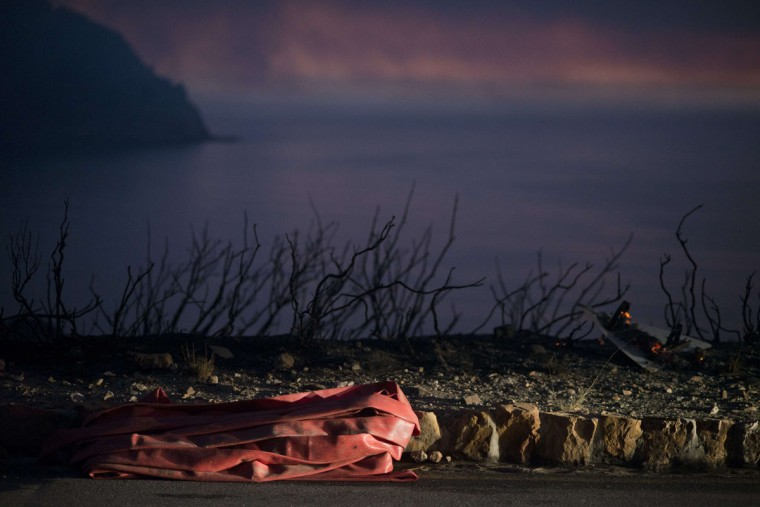 A fire hose lies next to a burnt sign on a road, after a fire in the mountains above Hout Bay, which was part of a larger bush fire raging in the mountains on the Cape Peninsula, on March 2, 2015, in the greater Cape Town area. (RODGER BOSCH/AFP/Getty Images)