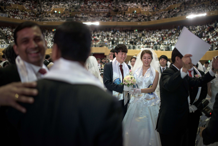 "Park Hyun-Sung, 31, and his bride, Park Jeong-Min, 28, wait for the start of proceedings at their seats in the venue of their mass wedding ceremony, at the headquarters of the Unification Church in Gapyeong early on Tuesday. Some 3,800 couples participated in the ceremony in Gapyeong, east of the capital Seoul. The church's mass weddings began in the early 1960s and at first involved just a few dozen couples, though numbers mushroomed over the years. The teachings of the Unification Church are based on the Bible but with new interpretations. The late founder Sun Myung Moon saw his role as completing the unfulfilled mission of Jesus to restore humanity to a state of ""sinless"" purity. (ED JONES/AFP/Getty Images)"