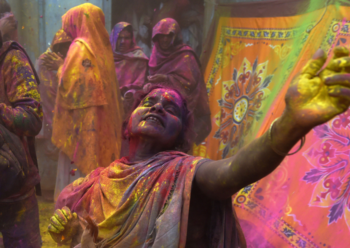 "An Indian widow dances as they celebrate Holi or ""festival of colors"" in Vrindavan on Tuesday.  Widows congregated on a small (ROBERTO SCHMIDT/AFP/Getty Images)"